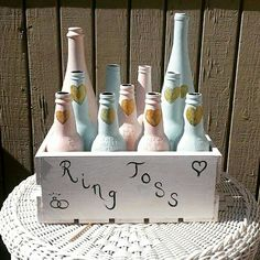 DIY  ring toss game for an outdoor wedding. Regular leftover indoor paint, wood crate from craft store, left over rootbeer and wine bottles. 2 coats on the bottles. With metallic gold hobby paint for accents! Voila! Wedding games, diy wedding