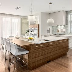Style galore, seating by the dozen, and Blizzard countertops aplenty! The more the merrier in this Weinhardt Friedemann, Design First Interiors kitchen.