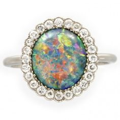 An Edwardian oval opal and diamond cluster ring, circa 1910.