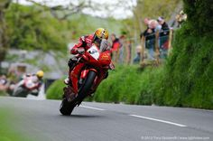 John McGuinness wheelies the red and black Joey Tribute Honda Fireblade at the top of Barregarrow during the Superbike TT race at the 2013 Isle of Man TT. Photo by Isle of Man TT photographer Tony Goldsmith. Wheel In The Sky, Football Outfits, Racing Motorcycles, Isle Of Man, Super Bikes, Street Bikes, Road Racing, Motogp, Race Cars