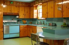 True restored mid-century modern kitchen, with knotted pine and light blue counters.
