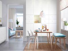 Eetruimte met veel licht, met essen tafel voor vier personen, in combinatie met essen bank en twee witte stoelen
