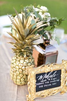 Beach wedding decorations: Spray painted gold pineapple on Hawaii wedding guest book table.