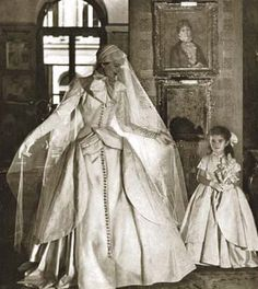 Brides.com: . 1950  Buttons and bows were the It details—the more the merrier. A tailored silk gown is festooned with rhinestones and a large ribbon tie.  Gown by Lanvin