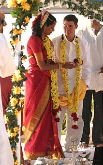 Sheela and John in Denver, CO. During the afternoon ceremony, held outdoors at the Denver Botanical Gardens, the khaki-clad groom and red-and-gold sari-bedecked bride exchanged garlands, symbolically giving themselves to each other.