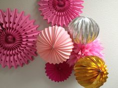 clustered of paper decorations for a girly baby shower party - accordion balls, pinwheel and tissue paper pom pom. Don't forget your fishing line!