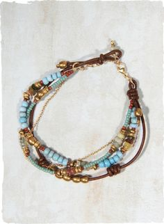 The multi-stranded bracelet is strung with semi-precious aquamarine, apatite and brass beads alongside a single leather strand and a delicat...