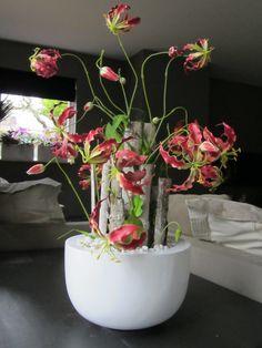 Prachtige zijden Gloriosa's opgemaakt in een hoogglans witte schaal en afgewerkt met wit grind. www.Abonneefleur.nl