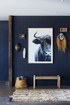Now trending: bold contrast between the black and white cow print and the dark wall. The various wood accents complete the look. This blue-black wall color was named the 2018 Color of the Year by PPG Paints, Black Flame