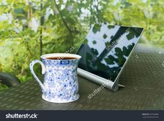 A Cup Of Tea And Digital Pad Web Tablet On The Table In Garden. Shallow Focus…
