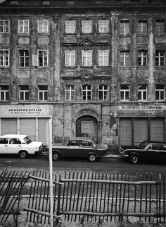 1990: This fence in Heringstrasse, Bautzen is threatening to collapse at any moment. The crumbling facade still shows the signs from old businesses. On the left a one-time laundrette, on the right a convenience store and tobacconist.