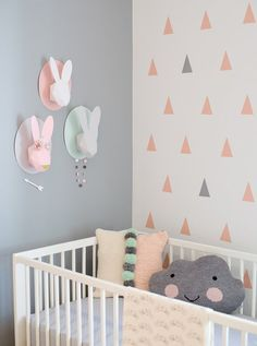 Gorgeous paper bunnies on the wall in this grey, pink and mint girl's nursery. Also love the triangle decals on the accent wall.