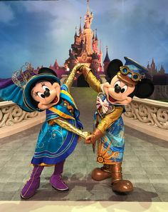 Mickey & Minnie posing with their arms spread out while wearing their amazing outfits in Disneyland Paris