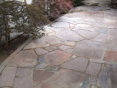 "This would be considered an informal look with stones ""placed"" rather than ""cut to fit"". Many people prefer this look with flagstone walkways and patios to add more character to their designs. Different coloured pieces to fill in the smaller gaps also has a nice effect. Picture compliments of www.american-stone.com"