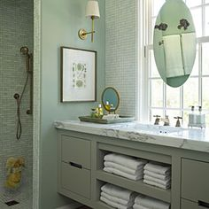 Suspending an oval mirror in front of the window allows natural light without losing function.    The overhead rain-style shower head and handheld sprayer are all controlled digitally, so guests don't have to fumble with unfamiliar fixtures.    Fixtures throughout all bathrooms share the same finish but in different styles, creating a custom but cohesive feel.