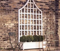 DIY Garden Trellis  very sturdy and elegant, costs, materials and tools list included in tute, along with drawings of how it goes together.    This would be nice against one of the blank walls in the courtyard shade garden, at a materials cost of approximately 134 dollars.