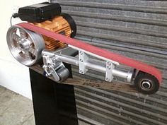 Linisher Homemade linisher powered by a 1 HP motor and incorporating a rubber end wheel, belt, bearings, and a spring