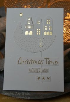 handmade Christmas card ... shimmery white and shiny gold ... die cut houses with golden windows ... mixed font sentiment on little panels ... funky and fresh look ...