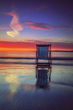 A beach chair facing the orange setting sun on the ocean. Beauty