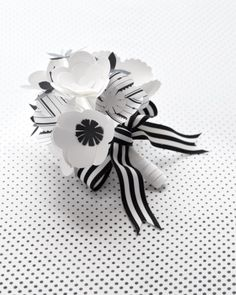 Paper blossoms bound with ribbon for the flower girls