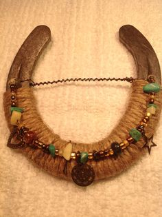 Rustic natural jute wrapped horse shoe wall hanging with turquoise and copper colored beads & charms.