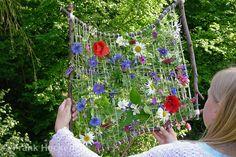 Kinder weben ein Blumenbild, Mädchen hat einen Rahmen aus Ästen gebaut, Wolle dazwischen gespannt und gesammelte Blumen eingewoben