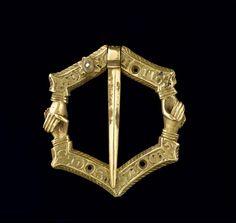 Fermail : hexagonal, mains croisées, inscription PÉRIODE 14e siècle TECHNIQUE/MATIÈRE ciselé , or (métal) , perle (matériau) DIMENSIONS Hauteur : 0.025 m Largeur : 0.027 m