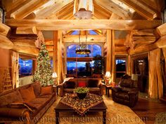 Greatroom with trusses and triple-stacked beams in what appears to be a round log post-and-beam home by Pioneer Log Homes of British Columbia
