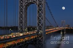 New York City's landmark, the George Washington Bridge along with a full moon during the blue hour.