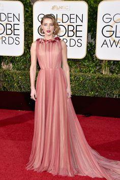Amber Heard en un vestido rosa con detalles florales de color rojo en el cuello y falda con caída y algo de cola, de Gucci.