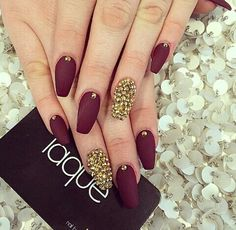 Maroon and gold nails.