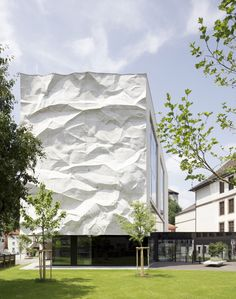 In Kufstein, Austria, there's a high school that first opened back in 1907 and recently underwent a very impressive renovation. Its south-east facade consists of a crinkled wall, a three-dimensional concrete structure resembling a sheet of crumpled paper hanging from the roof of the building.