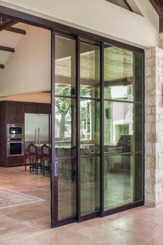 Large sliding steel doors obscure the boundary brining the outdoors inside and allowing guests to flow freely from interior living space to ...