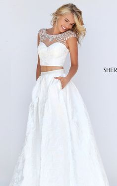 Radiate beauty and sophistication in this two-piece set gown, Sherri Hill 50197. Boat neckline of sheer fabric is bedecked with ornate beading draping over the cap sleeves. Sweetheart bodice will showcase your stylish best figure. Full ball skirt  is composed of textured fabric trailing down the full length hem with train.