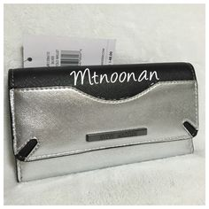 """Steve Madden Silver and Black Color Block Wallet NEW WITH TAGS, Steve Madden Silver and Black Color Block Wallet  • Color: Metallic Silver / Flat Black • Interior Colors: Black / Silver / Gold  • Dimensions: 8""""L x 4""""H x 1.5"""" • 12 credit card slots, 1 full length expandable slip pocket, zipper compartment and 2 exterior slip pockets • Gunmetal Tone hardware • MSRP $48.00 • Product ID: MR108619   I have more STEVE MADDEN, Check out my other items!  ❌ NO TRADES Steve Madden Bags Wallets"""