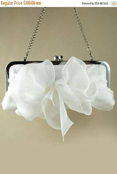 Silk light chiffon bridal clutch with side elegant bow and removable chain. Perfectly matched to silk bridal gown The body of this silk chiffon clutch is natural white. Also available in 26 colors of silk chiffon and can be a beautiful colorful compliment to bridesmaids dresses. Kiss lock nickel-free purse frame is good for anyone with sensitivity to nickel. Popular as wedding accessories: Bridal clutch, Bridesmaids Gifts, Mother of the Bride Purse, and even those attending the wedding as…