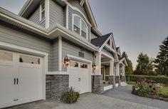 Grey siding, stone siding, white garage doors with windows, landscaping, two-story home | Clay Construction