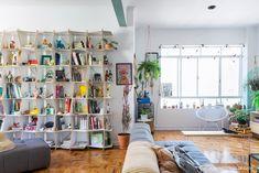 Sala integrada com estante modular branca e muitos acessórios coloridos