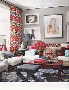 Displaying collections of artwork from floor to ceiling can really open up a small space. Love the pop of color on the table, windows and sofa. Just enough to carry the neutral grays in the room.