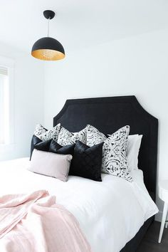 Chic black and white bedroom with pink accents boasts a striking black head board positioned against a white wall and accenting a bed dressed in white hotel bedding drapped with a pink throw and topped with black lattice pillows layered behind smaller black pillows and a light pink lumbar pillow lit by a black and gold pendant hung over the bed.