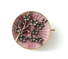 Fabergé! Circa 1899, this gold, enamel, and diamond brooch has a definite Japanese influence, with a branch of cherry blossoms sweeping over a circular base of starburst-engraved gold with translucent purplish-pink enamel. It's by Fabergé workmaster Oskar Pihl, and comes in its original silk- and velvet-lined case.