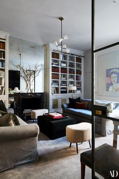 An Andy Warhol portrait of Queen Elizabeth II, a gift from Nonoo's father, holds court in the library alongside RH sofas and a midcentury Stilnovo pendant. Divider