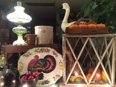 Fall Window Display: Crocks, Brown Stoneware, Turkey Platter from Italy, Primitive Wood Tray, Aladdin Lamp, Primitive Red Bench, Large Vintage Terrarium.