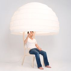 chair tucked inside a giant paper lampshade that can be folded down to create a private den.
