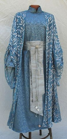 Aquatic Elven Outfit— The under robe fabric was a moire like rippling water with tone on tone leaves and silver cording at the sleeve and garment hem. The translucent lightweight silk over-robe was hand dyed from white to pale blue with silver leaves. The over robe bell sleeves can be gathered up with a blue shell shaped button and loop. A pewter scallop brooch and silver silk dupioni sash belt with cords, iridescent soap bubble like accents, beach glass beads and seashells complete the…