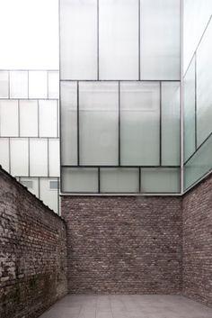 Die Glasfassade auf einem gemauerten Sockel des Altbaus