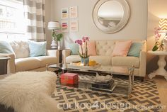 A little pink, orange and gold makeover. Clear coffe table, neutral walls and sofas and soft colos pilows made this living room very cozy.