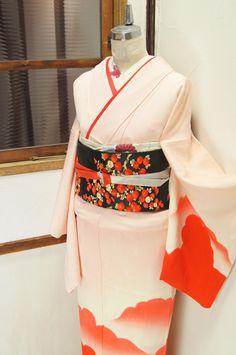 薄桜色に紅緋色の雲がふわりと湧き立つように染め出された付下げ着物です。