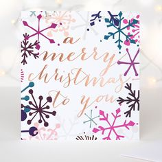 This modern luxury Christmas card features graphic snowflakes in purple, pink and blue hues and is complimented by a metallic copper foil script font message with the words A Merry Christmas to You.