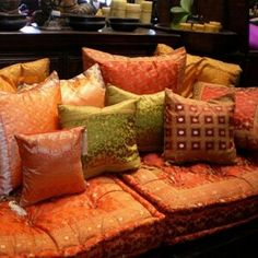 A very indian sofa decor complete with banarasi silk and colourful shiny cushions